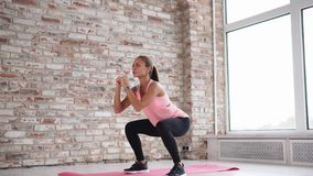 Young beautiful woman squats indoor.