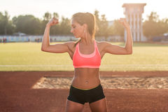 Fitness woman on stadium showing off muscular arms flexing biceps. royalty free stock photos