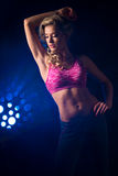 Fitness woman. Standing against color lights Stock Photo