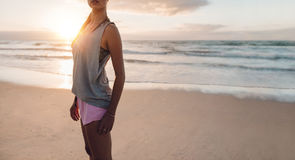 Fitness woman standing on the beach. Cropped shot of fitness woman standing on the beach. Sporty female on the sea shore in morning for workout Stock Images
