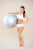 Fitness woman standing with gym ball Stock Photography