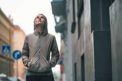 Fitness woman standing near building in city. Portrait of fitness young woman standing near building in rainy city Stock Photography
