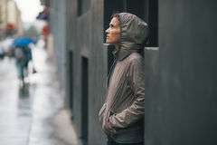 Fitness woman standing near building in city. Portrait of fitness young woman standing near building in rainy city Royalty Free Stock Photography