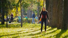 Fitness woman strength training doing workout at sunny autumn park. Fit caucasian sporty girl exercising her body -  squats Royalty Free Stock Images