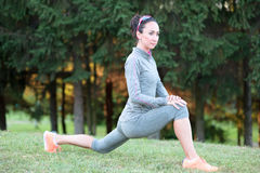 Fitness woman stretches during training exercise outdoor Royalty Free Stock Photography