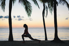 Fitness woman stretching on the beach in the morning. Fitness woman stretching for warming up before running at tropical caribbean beach in Riviera Maya, Mexico Stock Photo