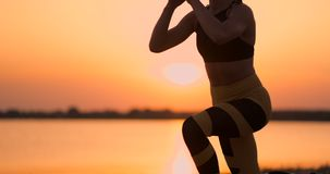 Fitness woman stretching doing lunge stretch exercise. Female athlete training lunges stretches outside in beautiful stock footage