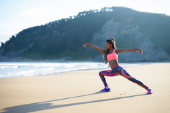 Fitness woman stretching and exercising at the beach. Fitness woman stretching legs and practicing dancing poses at the beach. Black female athlete working out Royalty Free Stock Photography