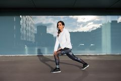 Fitness woman stretching and exercising in the city Stock Images