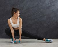 Fitness woman stretching at grey background indoors royalty free stock images