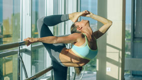 Fitness woman stretching in the gym. Barre Stock Image