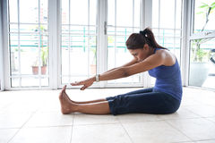 Fitness woman stretching her hamstring. Asian fitness woman stretching her hamstring while being on the floor royalty free stock photo