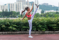 Fitness woman stretching her legs doing yoga standing split exercise outdoors in city park in summer. Royalty Free Stock Photography