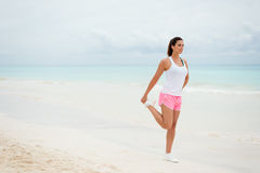 Fitness woman stretching legs at the beach Royalty Free Stock Images