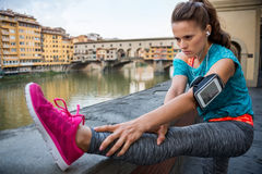 Fitness woman stretching near ponte vecchio in florence, italy Stock Photos
