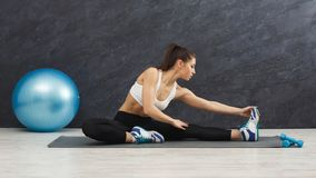 Fitness woman stretching indoors stock photos