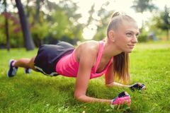 Fitness woman stretching and working out in park, on grass Stock Photography