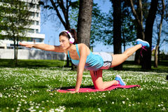 Fitness woman on stretching workout in park stock photo