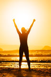 Fitness woman success. Fitness woman celebrating sport success on beautiful summer sunset or morning on the beach.  Successful female runner silhouette raising Royalty Free Stock Image