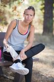 Fitness woman suffering painful ankle sprain injury after running. Female stock photography