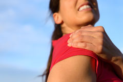 Woman shoulder injury. Fitness woman suffering from shoulder injury while exercising. Sky copy space background Royalty Free Stock Images