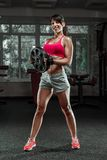 Fitness woman swinging kettle bell at gym Stock Photos