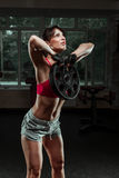 Fitness woman swinging kettle bell at gym Stock Photo
