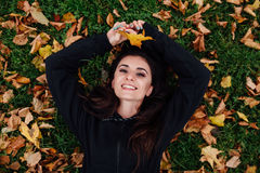 Fitness woman take a rest at fall park. Surrounded by autumn leaves on green lawn. Stock Photo