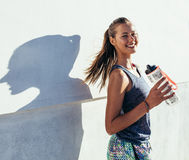 Fitness woman taking a break after running workout. Shot of beautiful female runner standing outdoors holding water bottle. Fitness woman taking a break after royalty free stock photography
