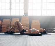 Fitness woman taking break after workout. Side view of fitness woman lying on floor. Muscular female relaxing after exercise training session Royalty Free Stock Image