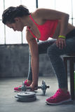 Fitness woman taking dumbbell from the floor in urban loft gym Stock Photos