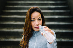 Fitness woman taking a workout rest for drinking water Royalty Free Stock Image