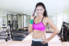 Fitness woman talking on cellphone at gym Stock Images