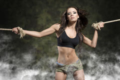 Fitness woman with tied arms with smoke and military shorts Royalty Free Stock Image