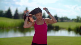 Fitness woman touching hair at park in slow motion. Portrait of asian girl stock video