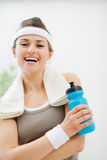 Fitness woman with towel holding bottle of water Stock Photos