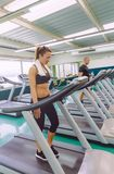 Fitness woman with towel training on a treadmill Royalty Free Stock Images
