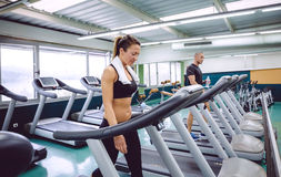 Fitness woman with towel training on a treadmill Royalty Free Stock Image