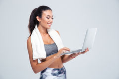 Fitness woman with towel using laptop Royalty Free Stock Images