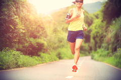 Fitness woman trail runner running on forest trail Stock Image