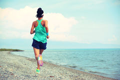Fitness woman trail runner running on seaside. Healthy young fitness woman trail runner running on seaside royalty free stock images