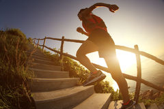 Fitness woman trail runner running on seaside mountain stairs Stock Photography