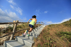 Fitness woman trail runner running up on mountain stairs Stock Image