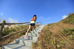 Fitness woman trail runner running up on mountain stairs Stock Photo
