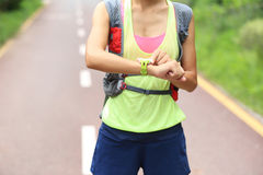 Fitness woman trail runner set her sports watch on trail Royalty Free Stock Photo