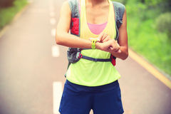 Fitness woman trail runner set her sports watch on trail Royalty Free Stock Image
