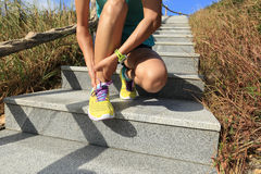 Fitness woman trail runner tying shoelace on mountain stairs Stock Image