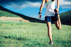 Fitness woman trail runner warming up Stock Photography
