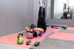 Fitness woman training abs workout doing lifts leg raise or flutter kicks exercise on floor at gym. stock photography