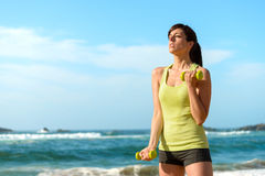 Fitness woman training biceps on beach Stock Photos